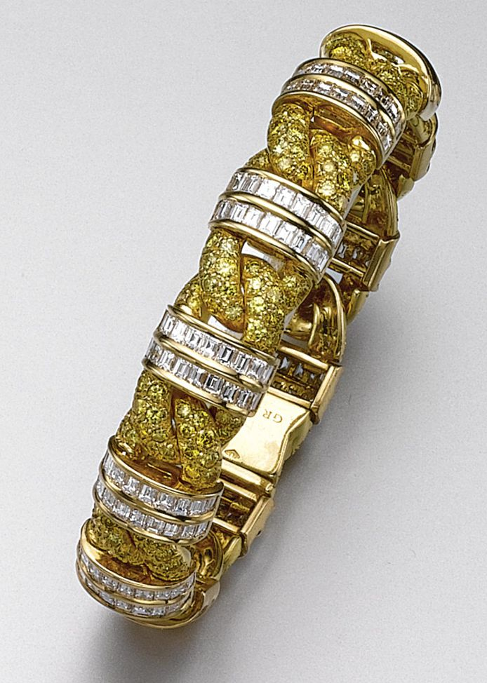YELLOW DIAMOND AND DIAMOND BRACELET, GRAFF. Designed as a braid, pavé-set with 243 round diamonds of yellow color weighing approximately 7.30 carats, decorated at intervals with bands of 198 square-cut near colorless diamonds weighing approximately 11.80 carats, mounted in 18 karat gold, length 7 inches, signed Graff.