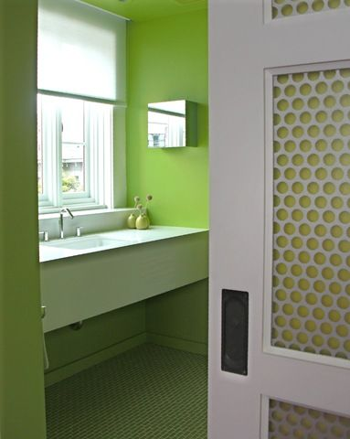 a clean and fresh green bathroom with designer fretwork pocket doors