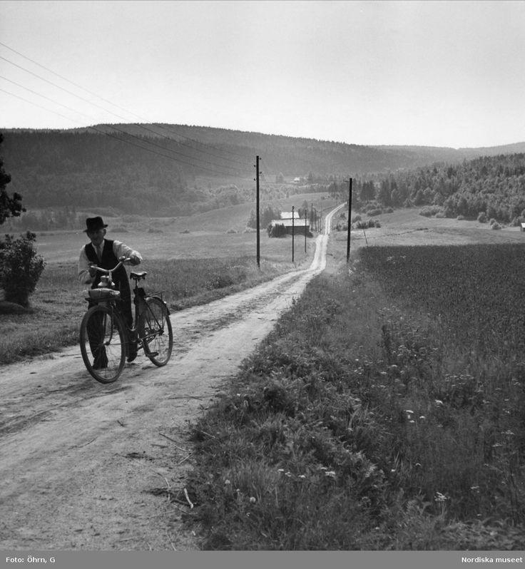 Äldre man styr cykeln uppför en liten backe. Landsväg.