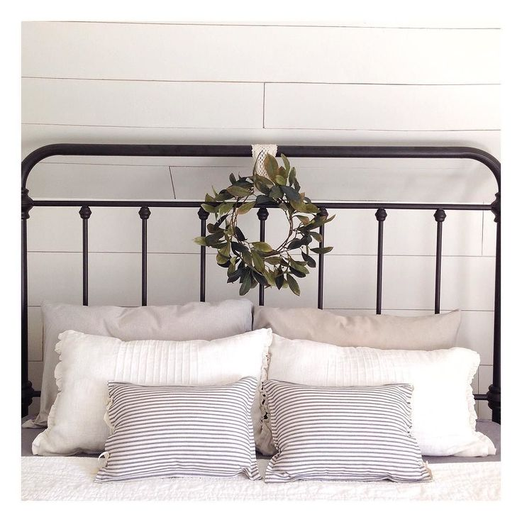 i am loving the stack of pillows and the charming wreath on this wrought iron bed frame goals for a guest bedroom during christmas time