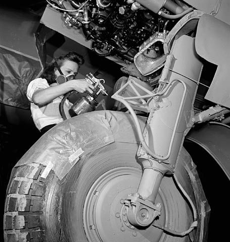 Female worker wearing face mask spray-painting the landing gear of a De Havilland Mosquito airplane on the production line. (item 1)