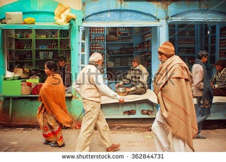 VARANASI, INDIA - JANUARY 4: Crowd of walking people on street with local shops with spices and medical products on January 4, 2013. Varanasi urban agglomeration had a population of 1,435,113
