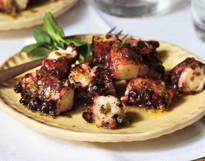 There's no reason to shy away from cooking octopus at home. It is as easy as boiling chicken. Every waterfront restaurant in Greece prepares it in this simple manner, first simmering it until tender, then searing it on the grill. If you buy fresh octopus, ask the fishmonger to clean it for you by removing all the viscera from the head. Frozen octopus is cleaned before freezing.