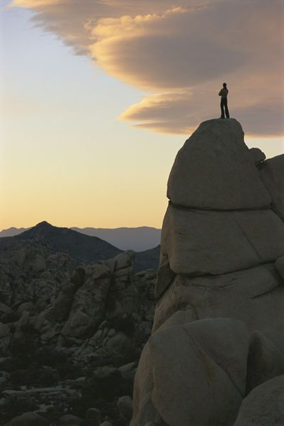 """A climber watches the sunset from high atop a rock formation."""" by National Geographic"""