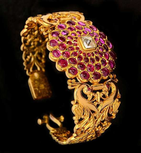 This heavy weight 22 carat gold kada with beautifully carved peacoocks and studded with burmese rubies is a make from Karni Jewellers Hyderabad. Weight: 80 grams Price: Approx 4 Lacs #GoldJewelleryHeavy