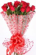 Hand tied bunch of 12 Red Roses with seasonal fillers wrapped in cellophane with a ribbon bows.