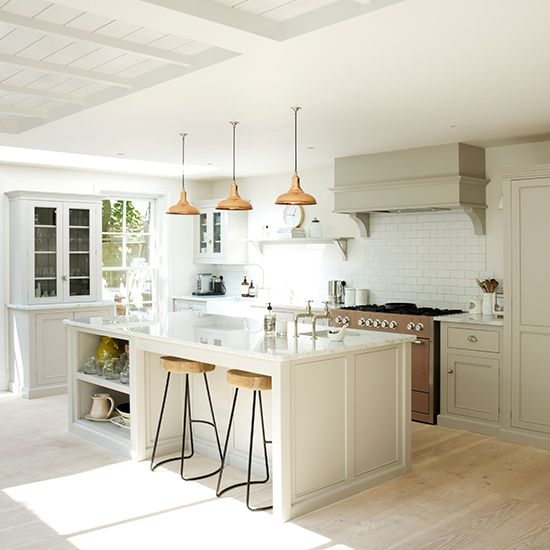 White kitchen with neutral cabinetry, white island unit, white worktops and copper pandant lights
