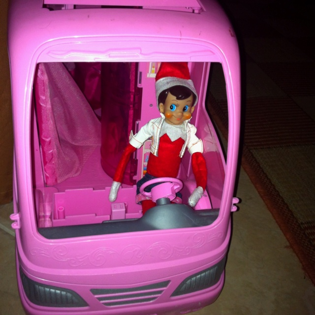 Elf on the Shelf driving Barbie's camper and wearing her clothes....