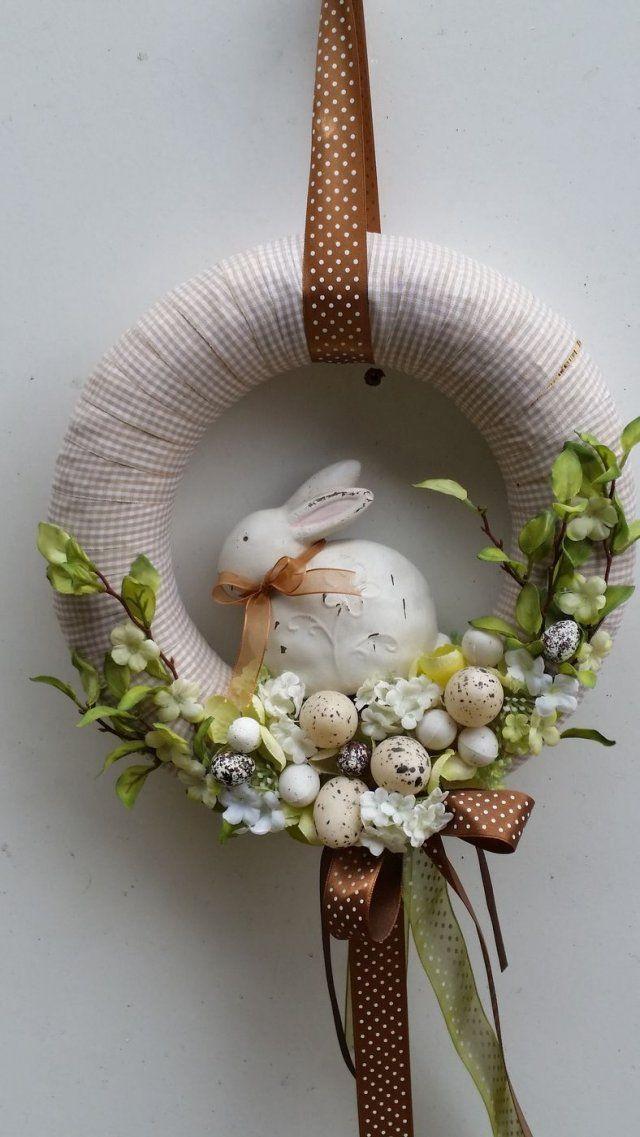 Wiosenny wielkanocny wianek wykonany na słomianej bazie, owinięty wstążką w kratkę. Uroczy zajączek przyciupnięty wśród atrybutów wiosny: gałązek, kwiatów hortensji i jajeczek. Średnica około 25 cm