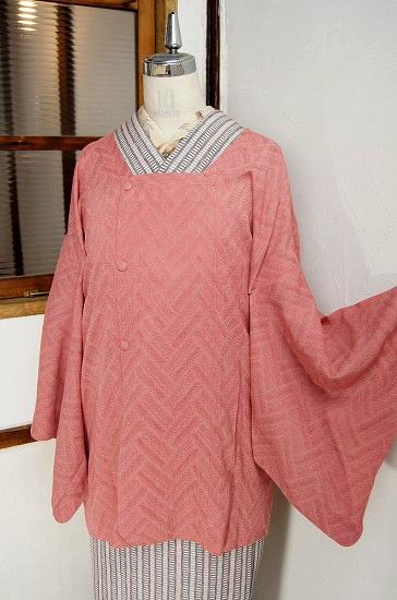 スモークがかった、ふわりと優しいい落ち着いたムードの淡いピンク色に、積み木のように組み合わされたモダンジグザグ模様が浮かび上がる薄物の紗の夏の道行コートです。