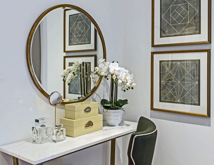 Enchantingly feminine, this beautiful bedroom dressing area is elegantly designed, the square framed prints contrasting effectively with the rounded mirror in brass.