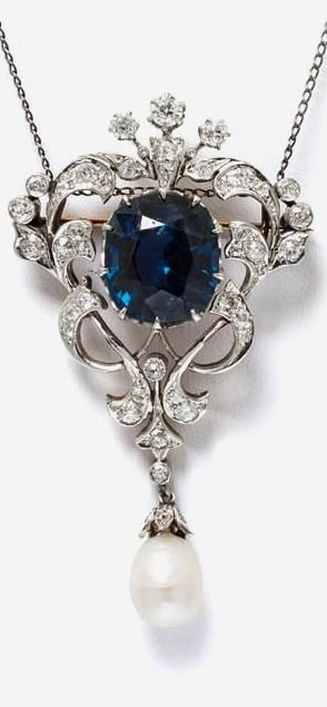 An Edwardian Platinum Topped Gold, Natural Blue Spinel and Diamond Pendant/Brooch, containing one cushion cut greenish blue spinel in a multi claw prong setting within an interwoven foliate motif openwork surround and hinged drop containing numerous old European and old single cut diamonds together with a drop shape baroque pearl (origin not tested), gold brooch fittings, suspension hooks allow wear as pendant.