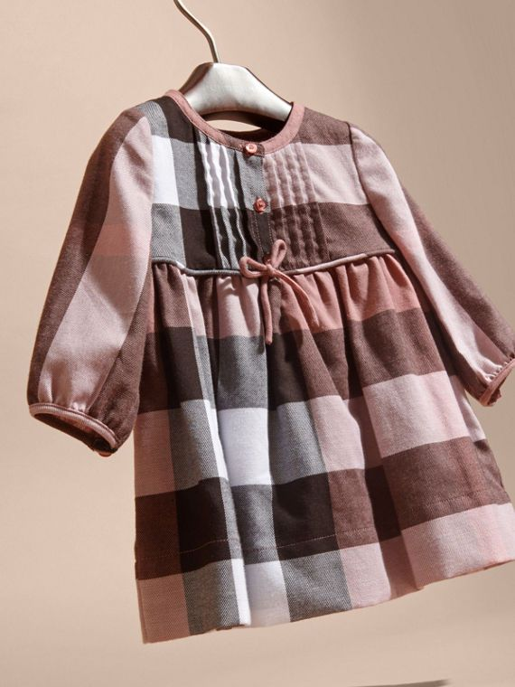 A Burberry check dress in Antique rose created in soft cotton flannel with an A-line silhouette. For all-season wear, it is sweetly detailed with a bow at the waist and a pleated bib.