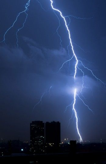 Huge lightning bolts dwarf tall building over Quezon City in the Philippines.