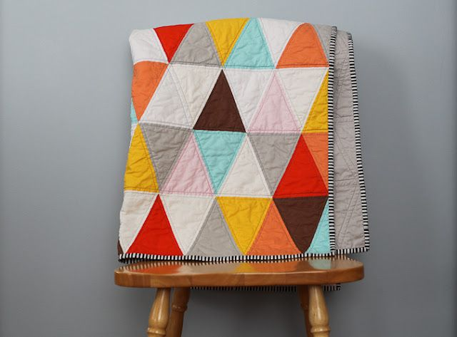Love this quilt, the colors, the simple triangle motif, the neutrals, the stripey binding...