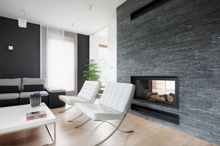 White Chairs and Grey Sofa near White Table and Black Fireplace