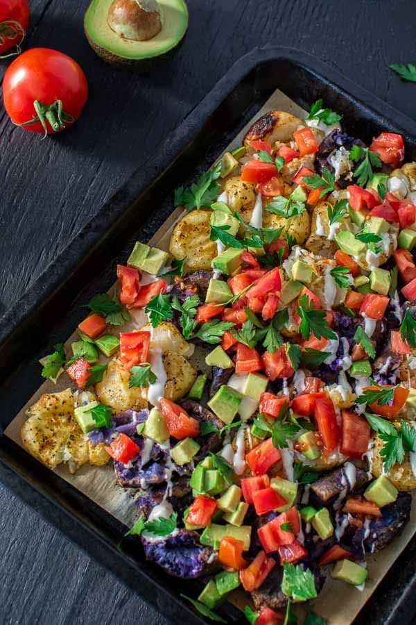 Delicious and colorful baked potatoes, topped with blue cheese dressing, juicy…