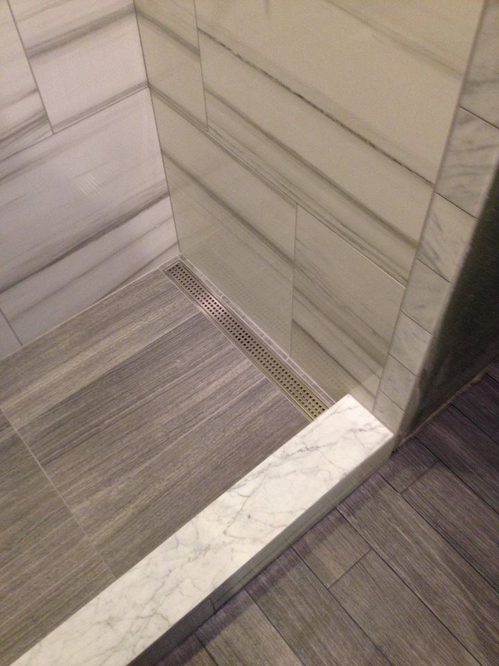 """Incorporating a linear drain into your shower allows you to slope the floor one direction, rather than using a curved funnel shape. You can use larger tiles, less grout lines. A funnel in that shape is no fun to build, let alone look at or use. With the drain down on one end, it makes the shower look and perform so much better.  Can also install """"tiled in"""" where the stainless grate is replaced with a strip of the floor tile making the drain almost invisible."""