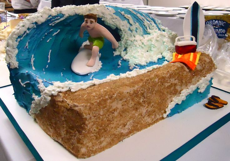 Surfing - This surfing cake was created with a rice crispy wave, modeling chocolate surfer dude, complete with and beach towel, flip flops and cooler for a cold one, all mad of sugar paste. The cake was covered in buttercream then airbrushed, and finished off with cane sugar for sand.