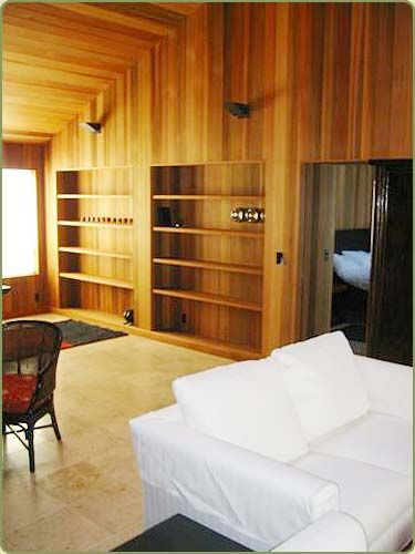 picture of a livingroom with wall paneling and shelves built of red cedar tongue and groove