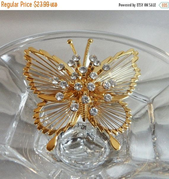 This #vintage Monet butterfly brooch is spectacular!   It features a gold tone wire butterfly that is open work, and the center has a burst of clear rhinestones on stems.   ... #ecochic #etsy #jewelry #jewellery #holiday2014etfs