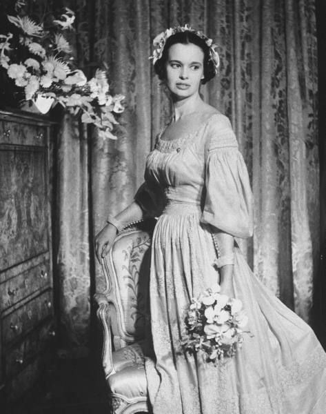 Gloria Vanderbilt Wedding Heiress, poet, actress Gloria Vanderbilt, standing w. hand resting on the back of an elegant chair as she poses in 1830 beige wedding gown of French linen after exchanging vows w. third husband, movie director Sidney Lumet, at apartment. Location:	New York, NY, US Date taken:	August 28, 1956 Photographer:	Gordon Parks