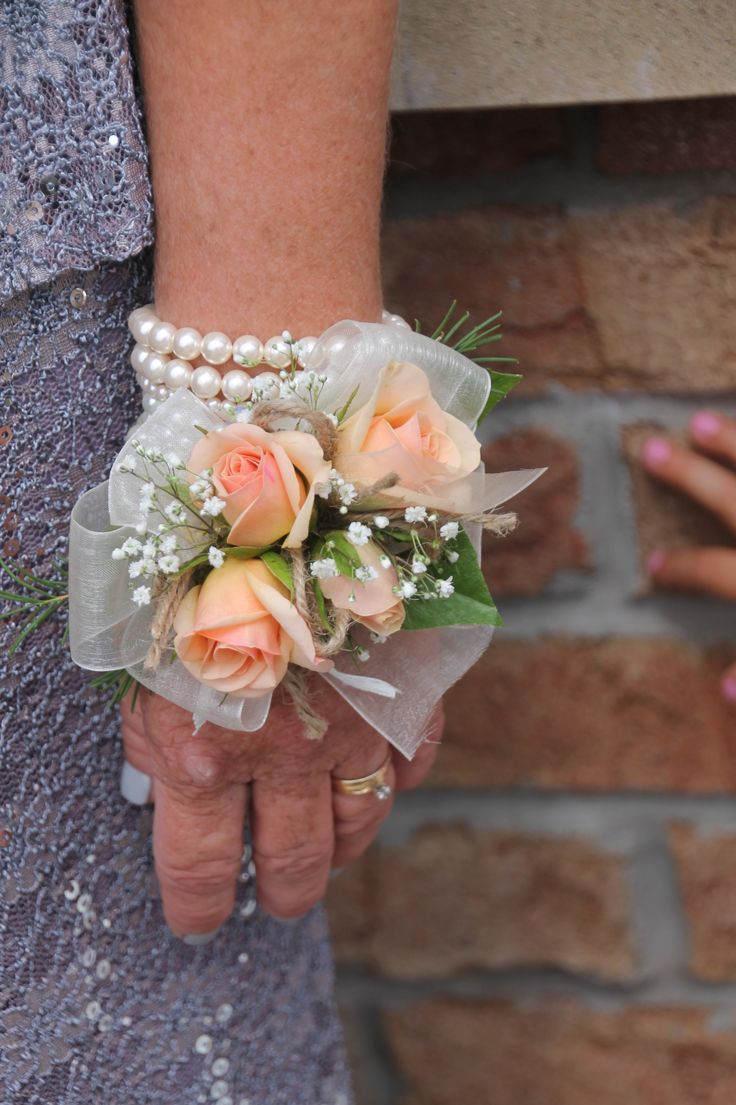 Peach mini garden roses & baby breath on pearl bracelet for a keepsake wrist corsage. Created by Judith Marie at Fox Bros Floral, Hartland, Wi