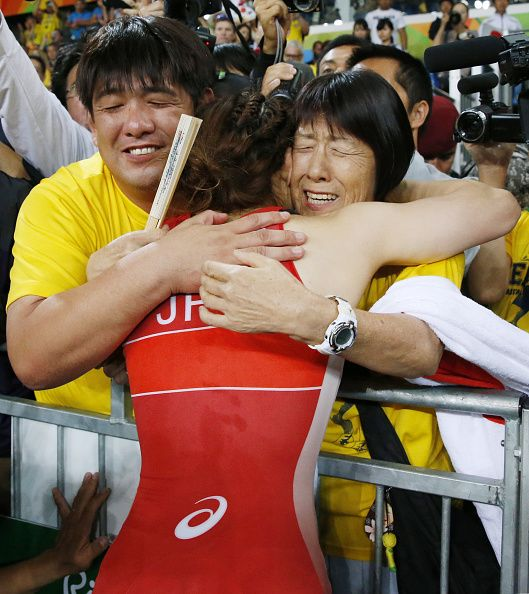 Silver medalist Saori Yoshida of Japan is embraced by her mother Yukiyo and…
