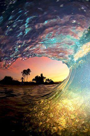 Clark Little, photographe surfeur hawaïen, réalise ses photos à l'intérieur des vagues. Ici le premier plan est éclairé par la lumière d'un flash stroboscopique tandis que le fond est illuminé par un coucher de soleil spectaculaire. ©  Clark Little