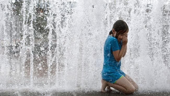 Evelyn Levitt, 7, cools down in the Old National Bank's fountain June 25, 2012 in Evansville, Ind. When her summer camp's planned trip to an amusement park was cancelled due to heat, they decided to visit the downtown fountain instead.