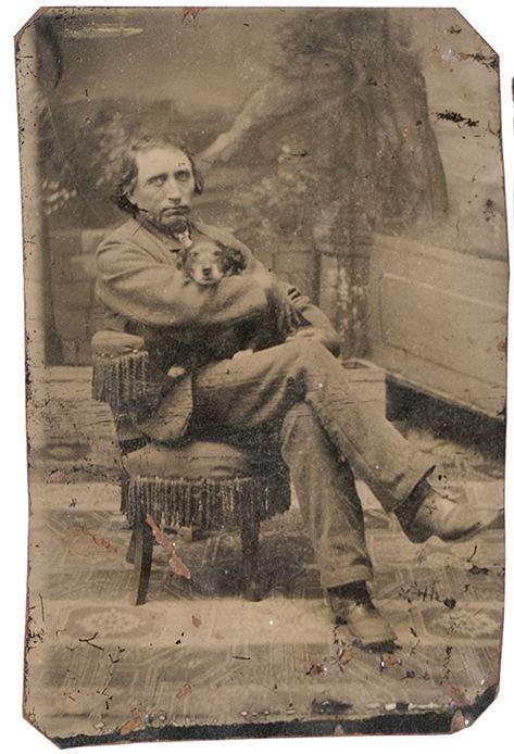 ca. 1870's, [tintype portrait of a man cradling his dog] via Cowan's Auctions