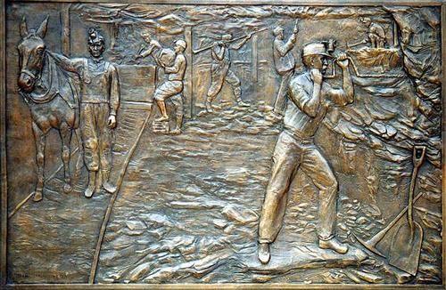 Memorial dos Mineiros de Antracite da Pensilvânia. Relevo em bronze. Zenos Frudakis (São Francisco, Califórnia, USA, 1951 - ). Encontra-se no Parque Girard em Shenandoah, Pensilvânia, USA. Vida subterrânea. é o painel da esquerda do monumento, e conta a história de mineiros trabalhando nas profundas minas carvão. Tem 1,8 m por 1,2 m.