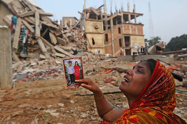 Horror in Bangladesh | A Bangladeshi woman weeps as she holds a picture of her and her missing husband as she waits at the site of a building that collapsed Wednesday in Savar, near Dhaka, Bangladesh, Friday. | Photo: Kevin Frayer/AP