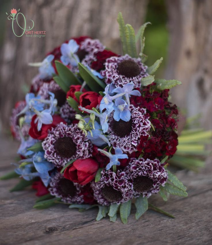 Hand tied bouquet in deep, vibrant hues. A romantic bouquet with boho flare.