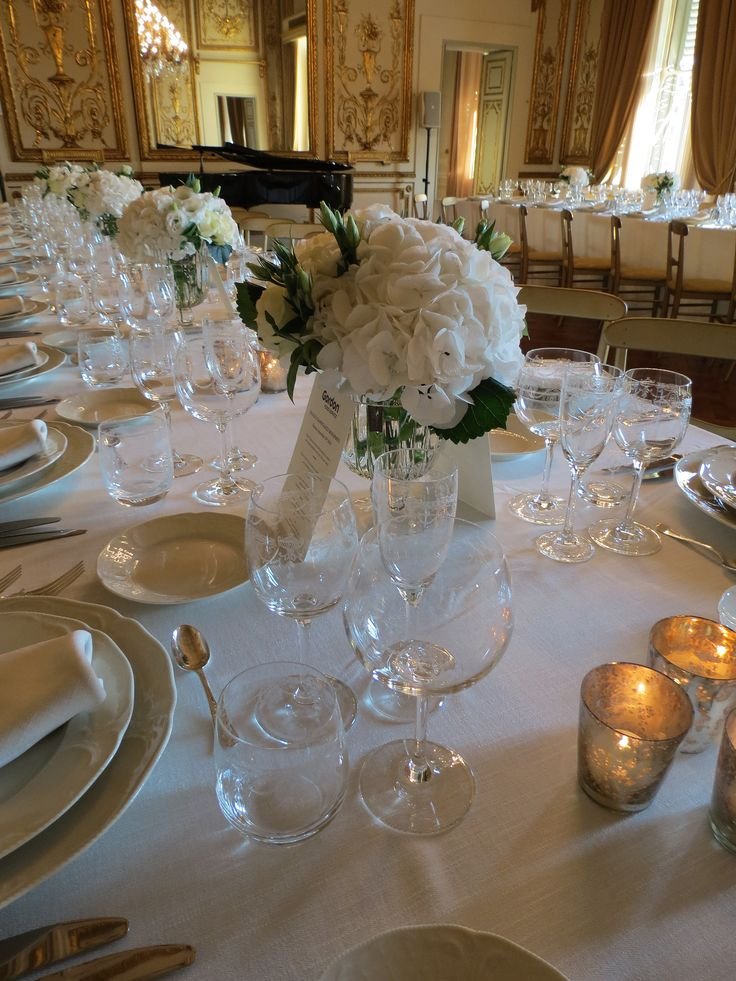 Glass vases with white hydrangea, roses and lisianthus.