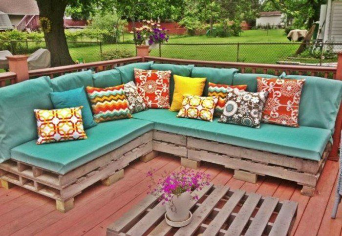 canapé en palette, suggestion excellente pour votre salon de jardin en palette, coussin d'assise vert, coussins multicolores, table basse en bois