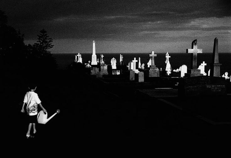 Trent Parke. AUSTRALIA. Sydney. A young boy carries a watering can in Waverley Cemetry. From Dream/Life series. 1998. Magnum Photos
