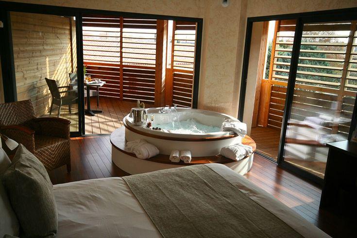 Chambre avec jacuzzi privé et décor en bois au Clarion Suites Narbonne Ile du Gue à Narbonne