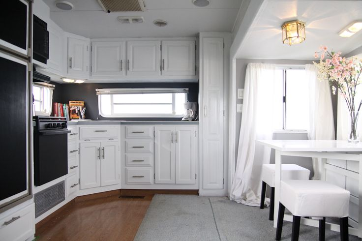 I don't prefer white cabinets in a house, but they seem to be just the thing for making an RV look larger. And the dark gray makes the wall disappear.  Lovely!