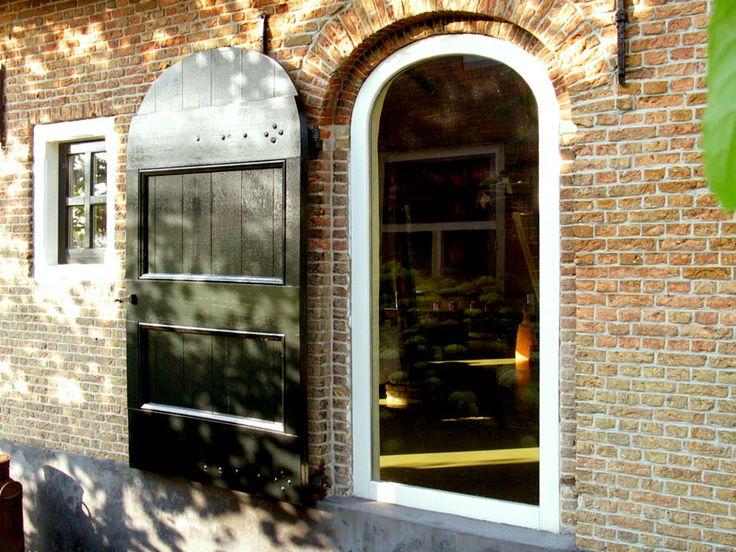 Kozijn met vast glas in oorspronkelijke deuropening, luik tegen gevel