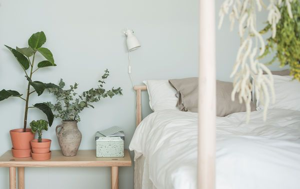 Nærbilde av en seng med naturlige tekstiler i lyse farger mot en lysegrønn vegg og et lavt nattbord med planter og en oppbevaringsboks