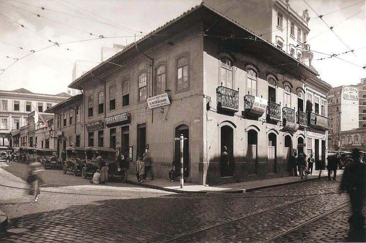 Entorno da Praça da Sé, vista de uma parte da fachada lateral do Governador Hotel (ainda existente) que pode ser vista por cima do casarão colonial no centro da foto. No canto direito (ao fundo), podemos ver o Palacete São Paulo e um pequeno sobrado que seria demolido em breve para a construção do edifício Piratininga, que foi inaugurado em 1929.