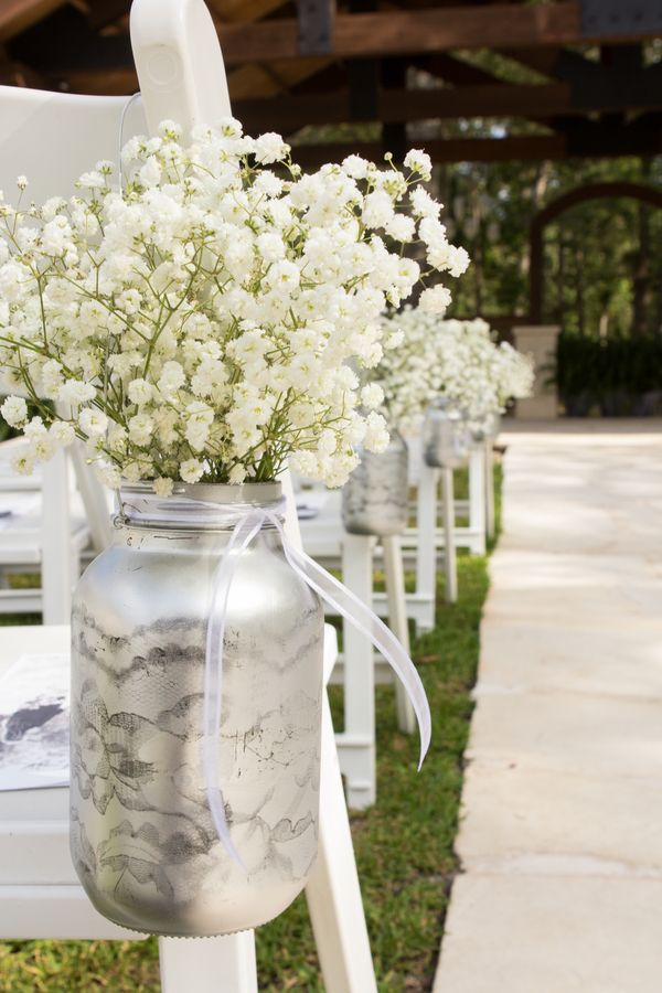 mason jars are painted silver and filled with baby's breath to line the wedding aisle - thereddirtbride.com - see more of this wedding here