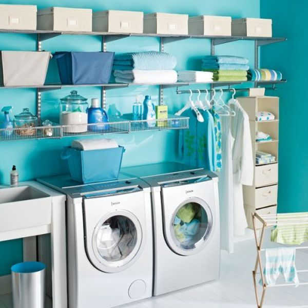 Blue laundry room wit plenty of shelf space