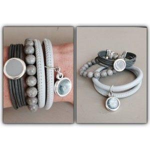 Een neutraal gekleurde set in een zachte kleur grijs. De set bestaat uit drie armbanden, één wikkelarmband van nappaleer met een munt bedel en met een magneetsluiting, één armband van veters met een kapittelsluiting en een mooie schuiver waar ook de kleur grijs weer in terugkomt en om de set compleet te maken nog een kralenarmband.