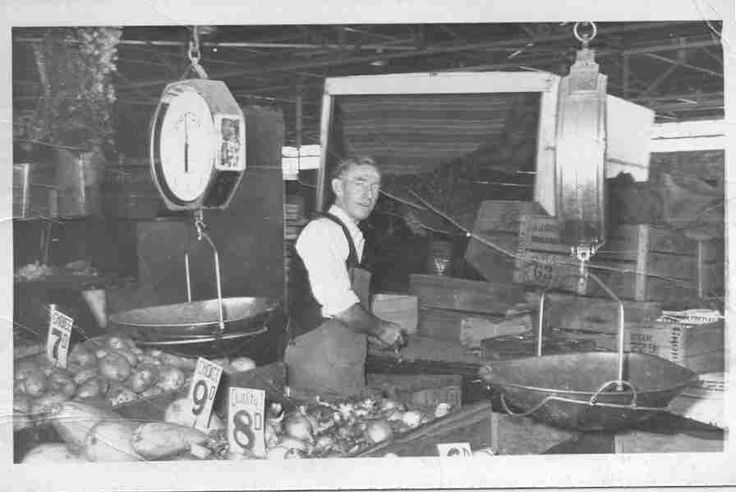 """James Byrne at Prahran Market stall, ca. 1955.  This was the Byrne family's vegetable stall at Prahran Market. The family had stalls 188 and 189, paying £ 5/4/8 rent per week in August 1964. Prior to this, James Byrne ran a second hand shop at the market selling """"furniture, tools, guns etc"""" [from docket]. This was stall 224, fronting Market Street and open daily."""