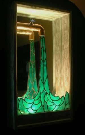 Shadowbox featuring emerald stained glass water rippling from a copper faucet