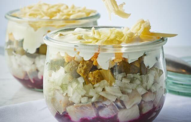 Śledzik pod pierzynką - sałatka śledziowa z jajkiem, cebulą, ogórkami konserwowymi, ziemniakami w mundurkach i gotowanymi burakami. Zwieńczona majonezem i startym na grubych oczkach serem żółtym.