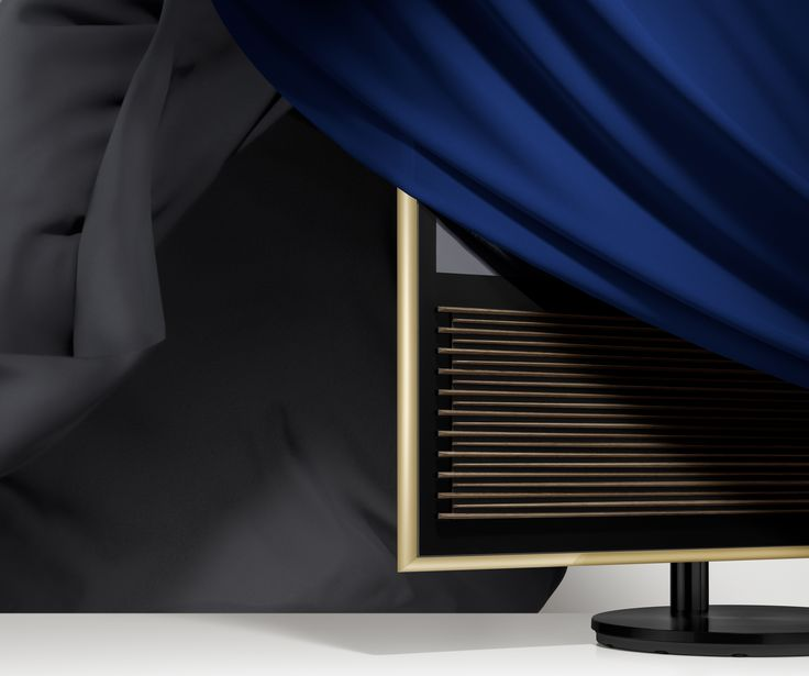 The soft glow from the Brass toned frame of BeoVision 14 is complemented by a matte black stand and speaker lamellas made from elegant smoked oak.