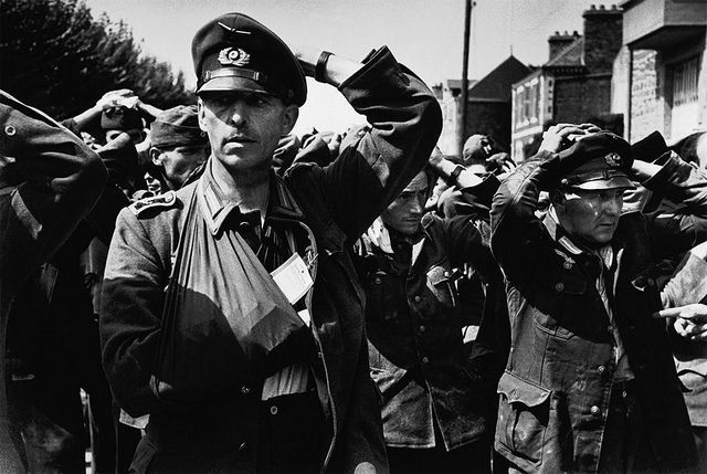 """1944, France, Saint Malo, Groupe de POWs allemands les mains sur la tête. A Dte, un """"Hauptfeldwebel"""", ou """"Oberfeldwebel der Truppe"""""""